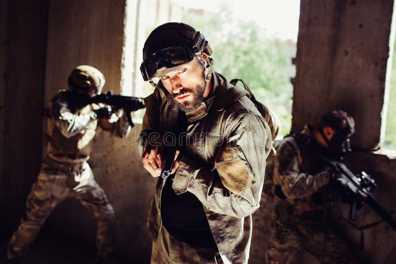 Le type barbu se tient dans une chambre noire et regarde au côté Il est terrifié L'homme tient le revolver en mains autre image libre de droits