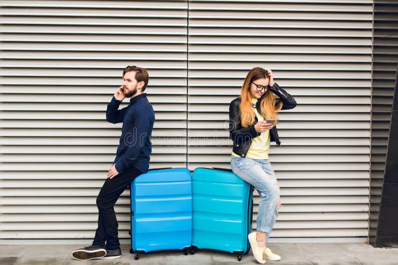 Le type beau avec la barbe s'est penché sur la valise sur le fond rayé gris et parler du téléphone cheveu de fille longtemps joli image libre de droits