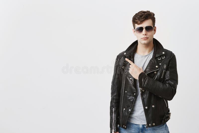 Le type beau sûr dans la veste en cuir noire avec des lunettes de soleil dessus, indique avec le doigt antérieur à l'espace de co image stock