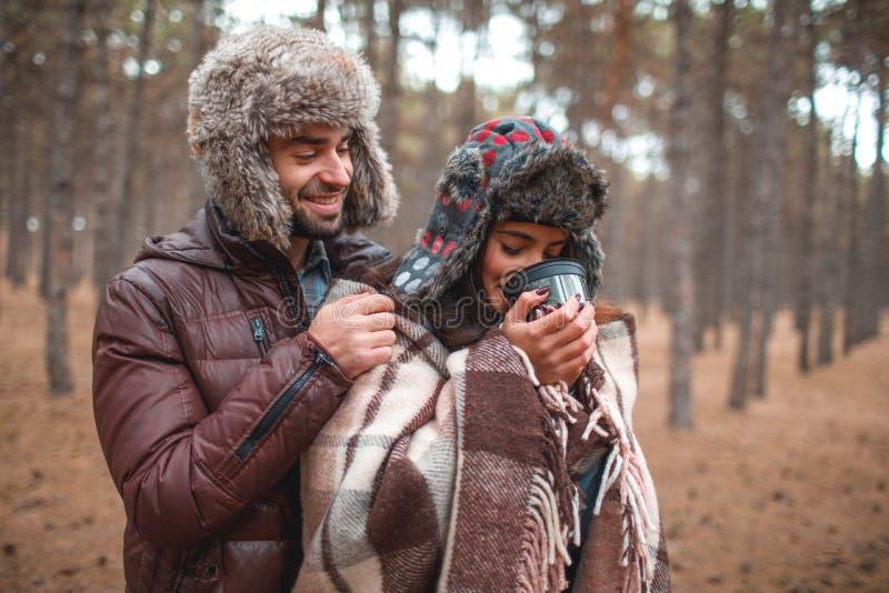 Le type cache la fille avec une couverture, le thé chaud de boissons de fille d'une tasse dans la forêt d'automne photos libres de droits
