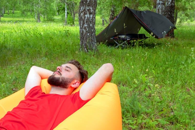 Le type dans le T-shirt rouge se trouve avec ses yeux fermés sur le sofa gonflable orange de Lamzatz Voyageur se reposant en natu photo libre de droits