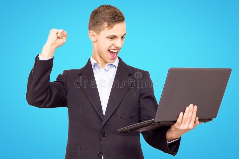 Le type dans une veste et une chemise bleue avec un ordinateur portable se réjouit, d'isolement sur un fond bleu photos libres de droits
