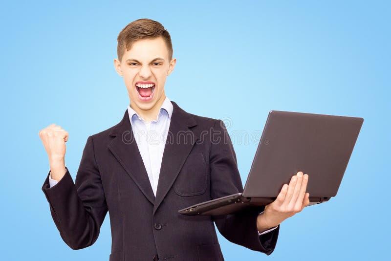 Le type dans une veste et une chemise bleue avec un ordinateur portable se réjouit, d'isolement sur un fond bleu photographie stock libre de droits