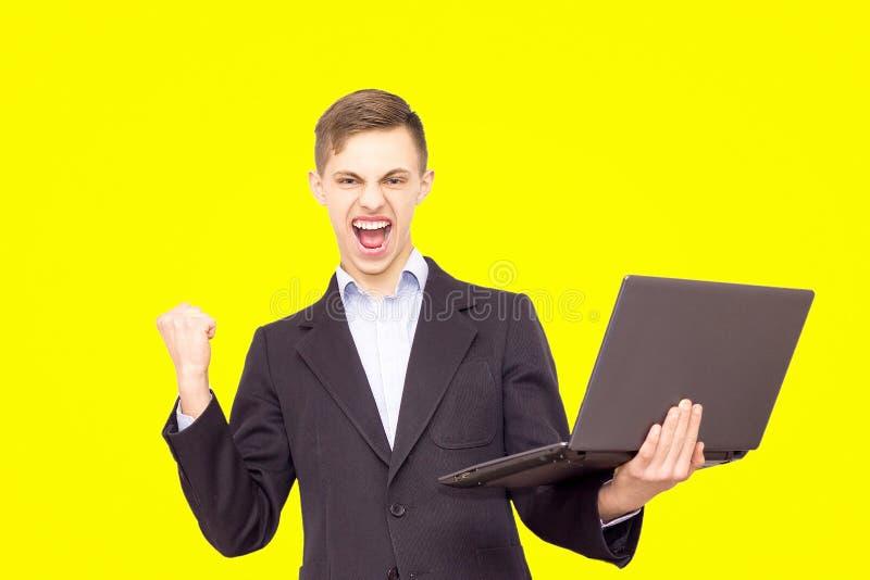Le type dans une veste et une chemise bleue avec un ordinateur portable se réjouit, d'isolement sur le fond jaune photographie stock libre de droits