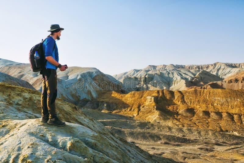 Le type de voyageur se tient au bord d'une colline sur le fond d'un paysage de montagne de désert image libre de droits