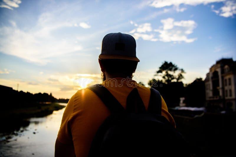 Le type devant le ciel bleu au temps de soirée admirent le paysage Appréciez le moment agréable Moment de prise pour admirer la n photo stock