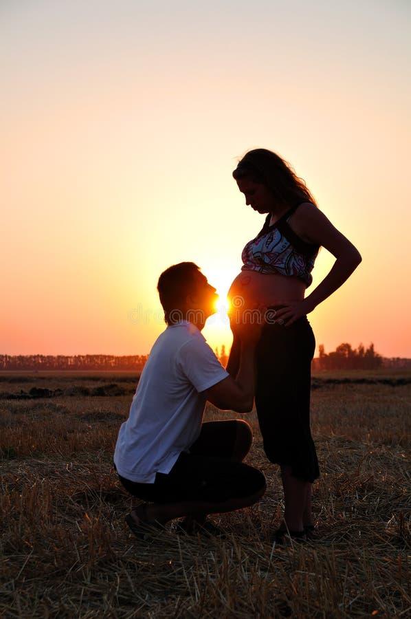 Le type embrasse un estomac de la fille enceinte photos libres de droits