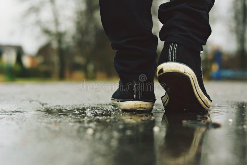 Le type entre dans des espadrilles sur la rue sous la pluie photo libre de droits