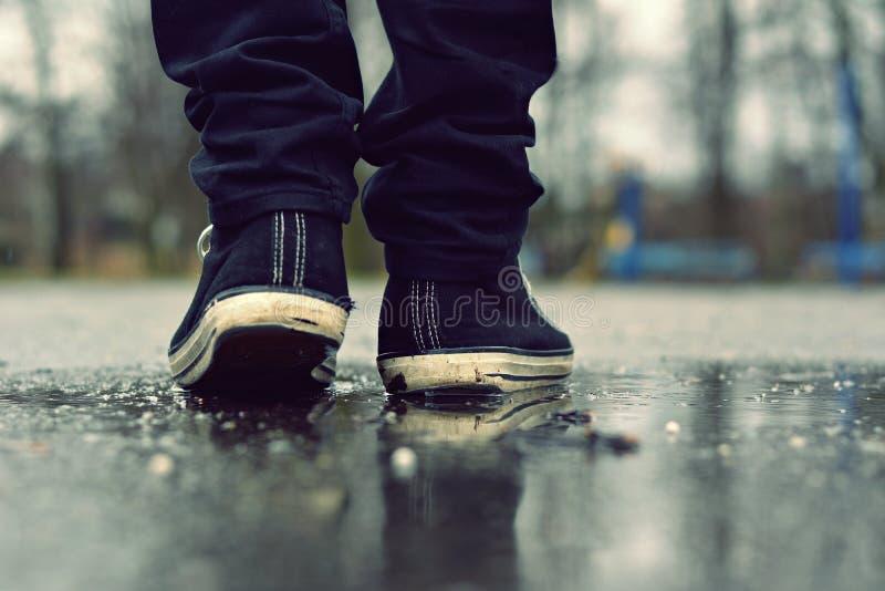 Le type entre dans des espadrilles sur la rue sous la pluie images libres de droits