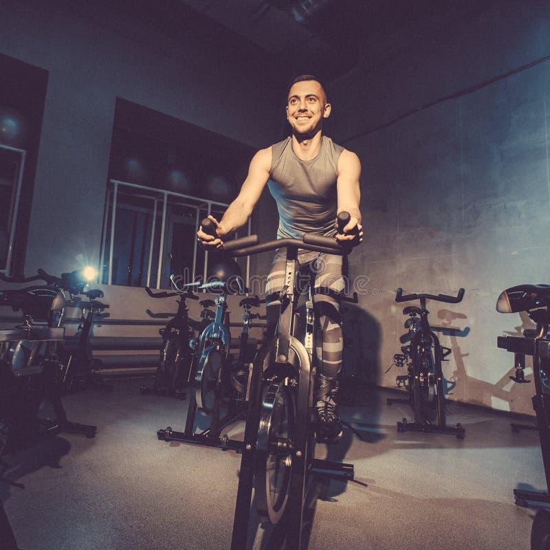 Le type est engagé dans un simulateur de bicyclette dans le gymnase Image modifiée la tonalité images stock