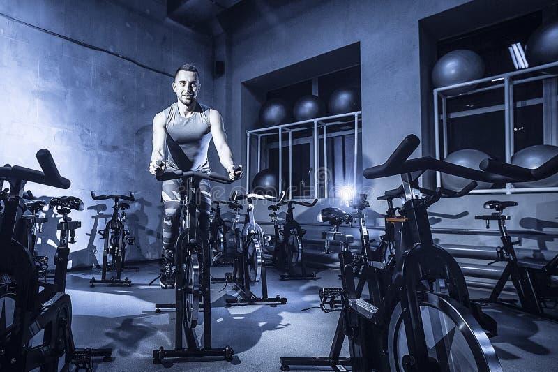 Le type est engagé dans un simulateur de bicyclette dans le gymnase Image modifiée la tonalité photos libres de droits