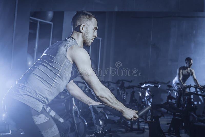Le type est engagé dans un simulateur de bicyclette dans le gymnase Image modifiée la tonalité photo stock