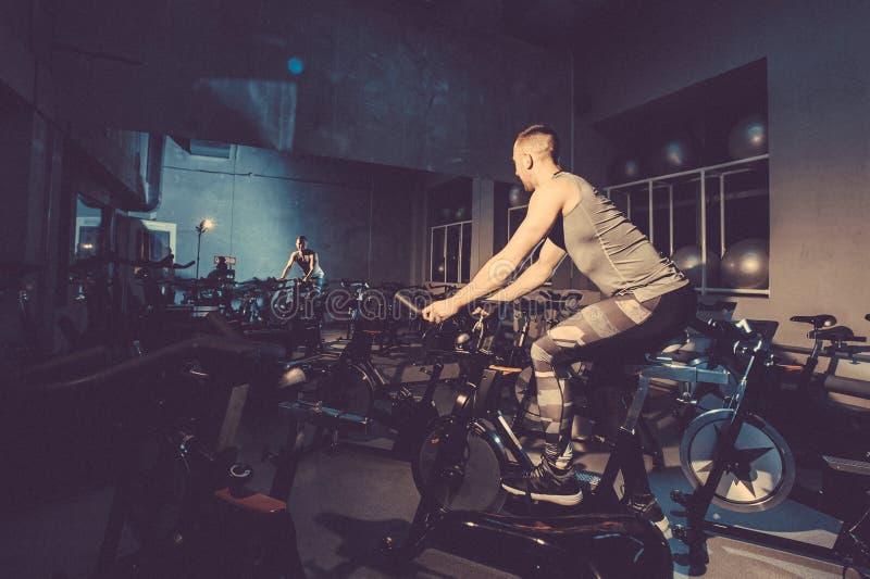 Le type est engagé dans un simulateur de bicyclette dans le gymnase Image modifiée la tonalité image libre de droits