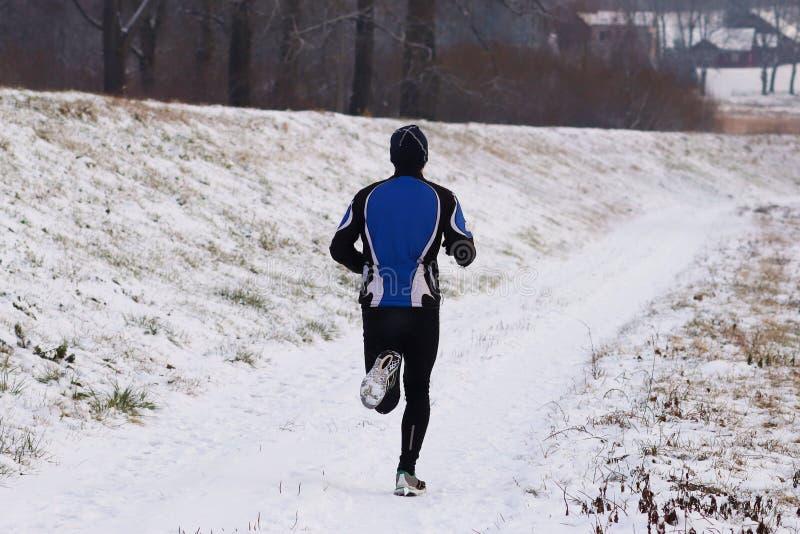 Le type est occupé à pulser dans les vêtements de sport dans la nature d'hiver Conditions atmosphériques extrêmes pour des sports photo libre de droits