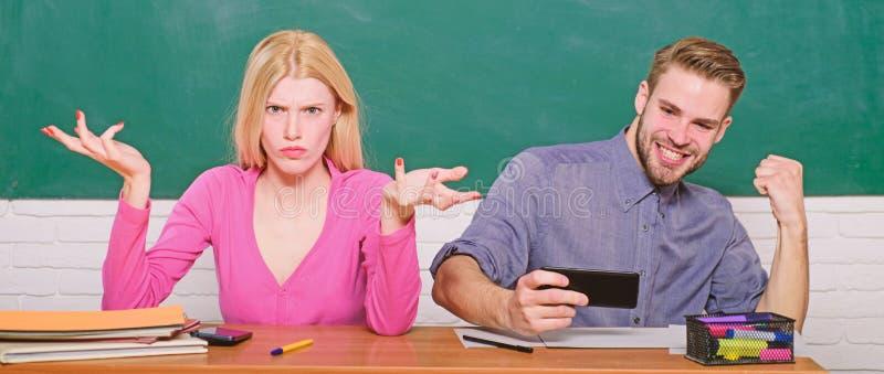Le type et la fille insouciants s'asseyent au bureau dans la salle de classe ?tude dans l'universit? ou l'universit? ?tudiants d' image libre de droits
