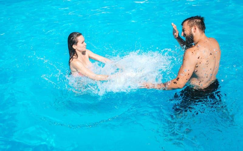 Le type et la fille jouent dans la piscine La fille se tient là et faisant l'éclaboussement de l'eau Le type protège ses yeux con photographie stock