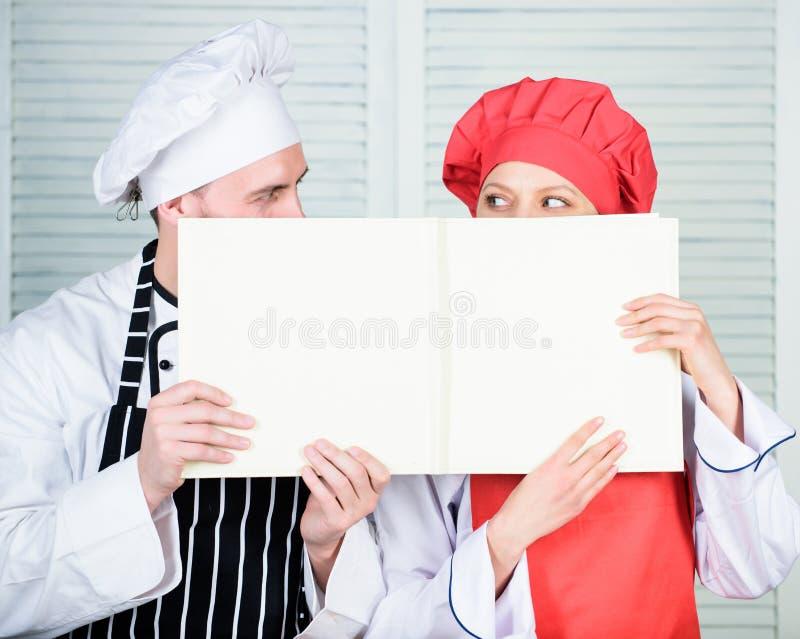 Le type et la fille ont lu des recettes de livre Concept culinaire La famille apprennent la recette r t photographie stock libre de droits