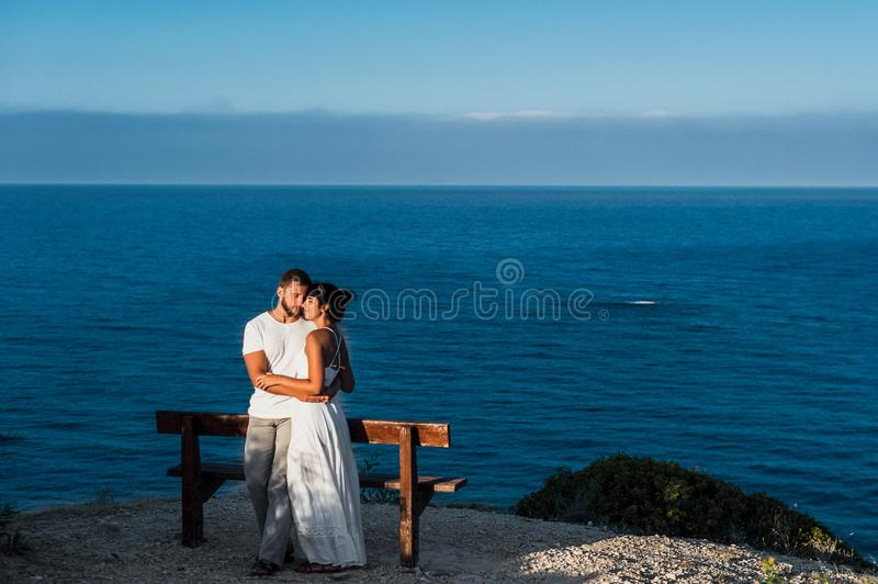 Le type et la fille rencontre les premiers rayons du soleil en mer photographie stock libre de droits
