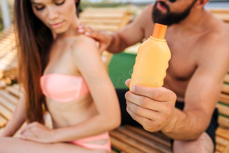 Le type et la fille sérieux s'asseyent Il met de la lotion de sunproof de la bouteille orange sur ses épaules et de retour elle r photos libres de droits