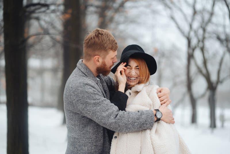 Le type et la fille se reposent dans la for?t d'hiver photographie stock libre de droits