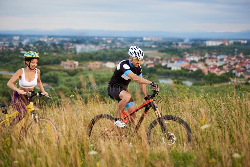 Le type et la fille sur des bicyclettes montent à la colline parmi l'herbe avec des wildflowers image stock