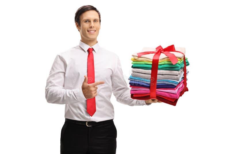Le type formellement habillé tenant une pile de repassé et d'emballer vêtent photographie stock
