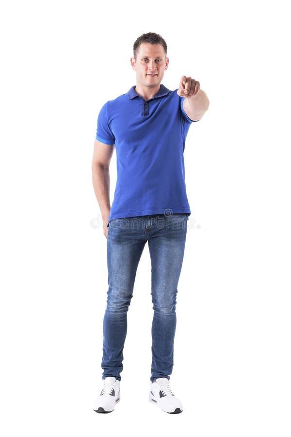Le type frais de sourire heureux dans le polo bleu dirigeant le doigt et regardant l'appareil-photo vous choisissent photos stock