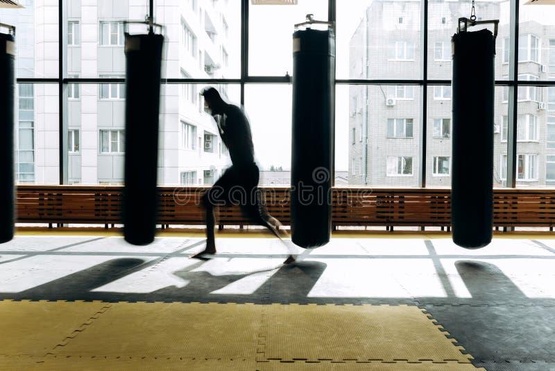 Le type habillé dans le T-shirt gris et les shorts noirs se tient sur la garde et établit un poinçon de boxe à côté du poinçon ac photographie stock
