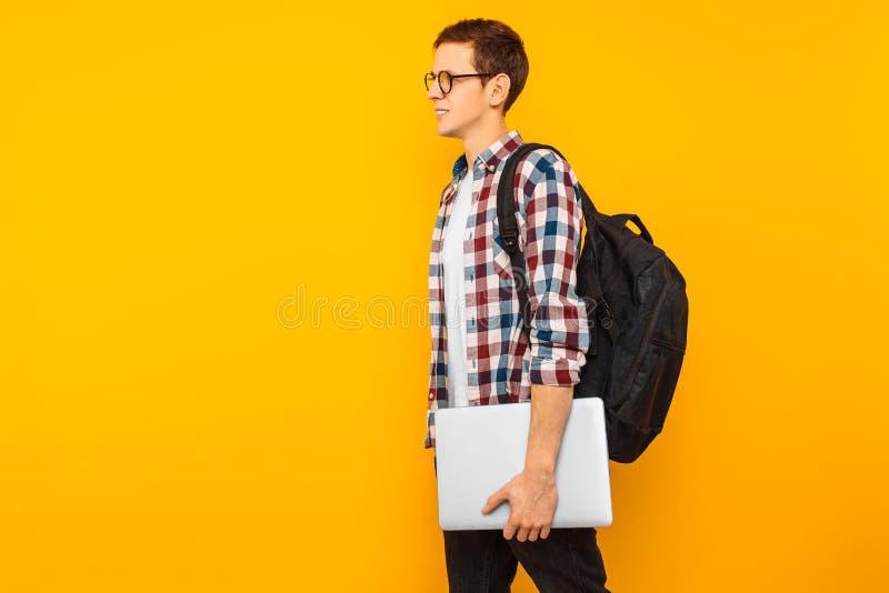 Le type heureux en verres, un étudiant dans une chemise de plaid, va avec un ordinateur portable fermé dans des ses mains, sur un photographie stock libre de droits