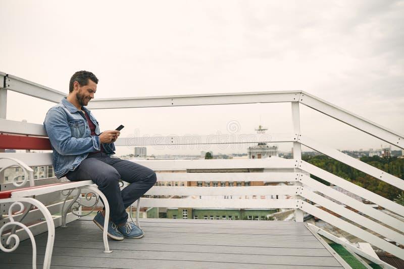 Le type heureux s'assied sur la terrasse mignonne dehors photographie stock