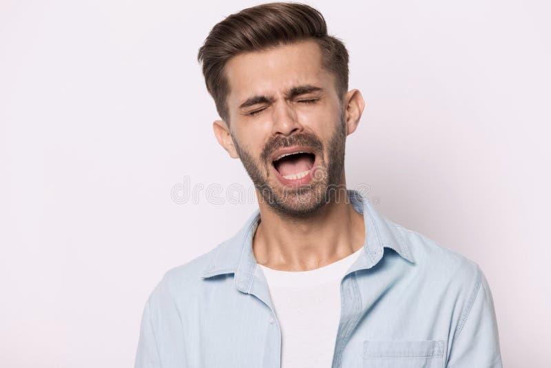 Le type hysterique a clôturé des yeux criards ou des gémissements d'isolement sur le blanc images stock