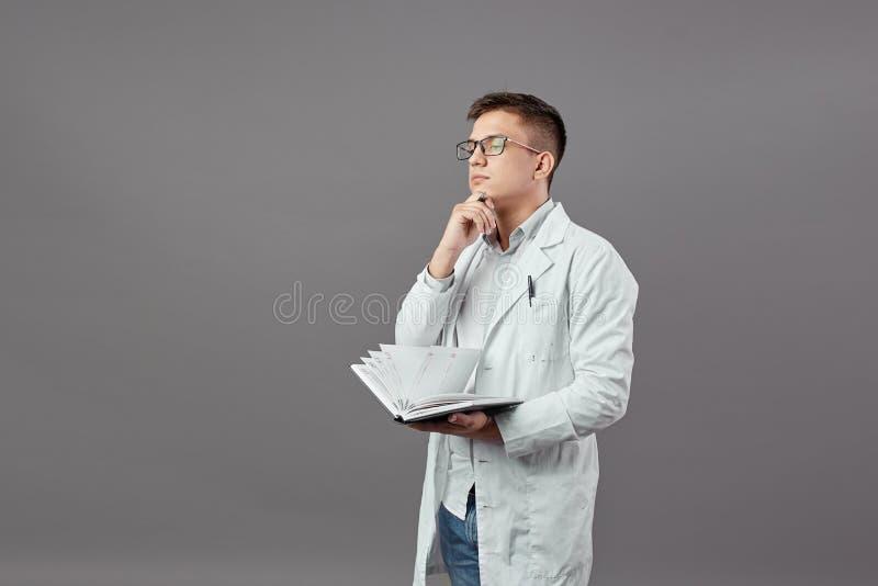 Le type intelligent en verres habillés dans une chemise blanche et un manteau blanc tient un carnet et pense sur un gris photographie stock