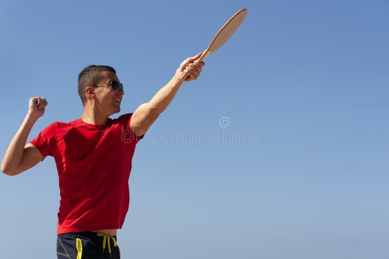 Le type joue le matkot sur la plage images libres de droits