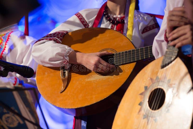 Le type joue un instrument folklorique ficelé photo stock