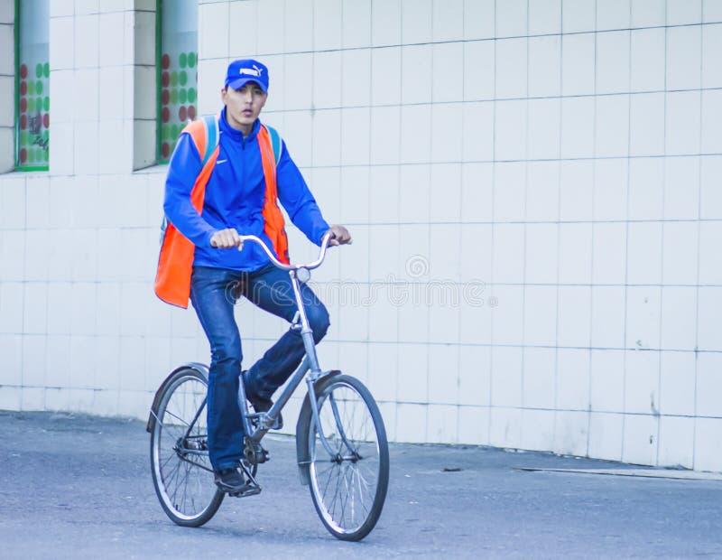 Le type monte un vélo sur le trottoir photographie stock