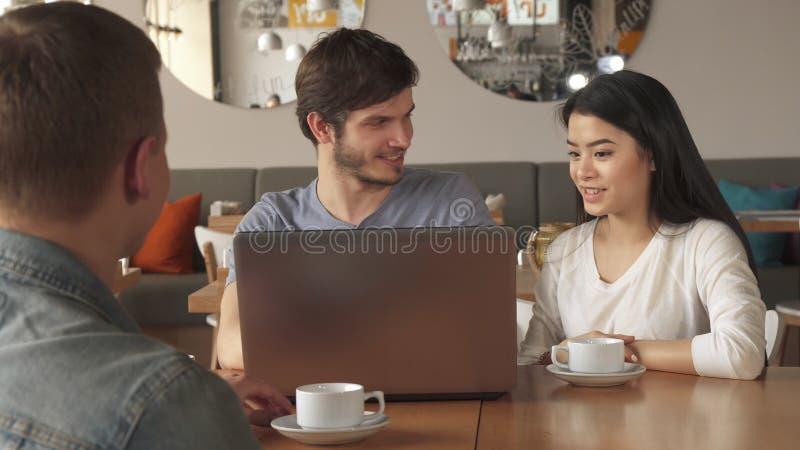 Le type montre quelque chose sur l'ordinateur portable à son ami au café image libre de droits