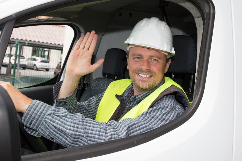 Le type occasionnel gai souriant heureusement montrant manie maladroitement vers le haut de se reposer dans une grande voiture bl photo stock
