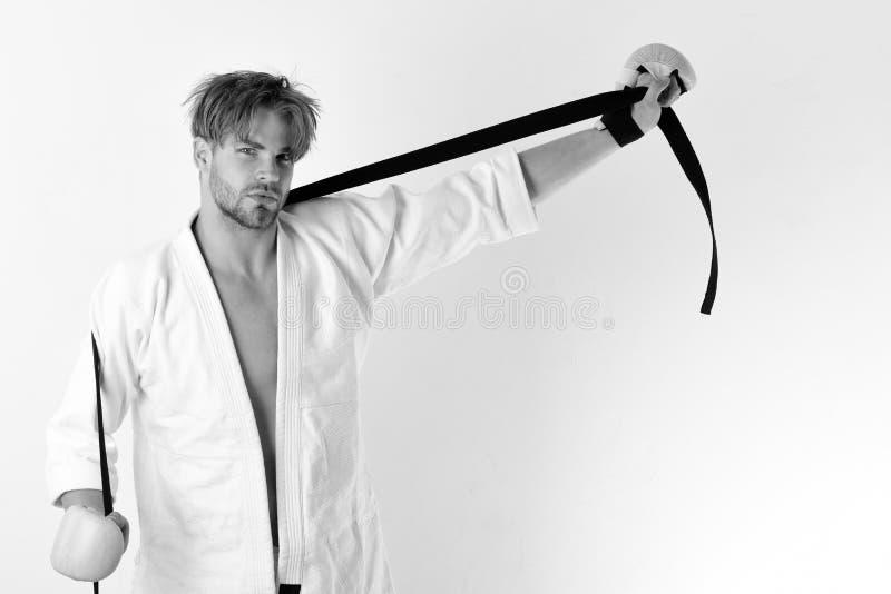 Le type pose dans le kimono blanc portant les gants de boxe d'or Concept mélangé d'arts martiaux Combattant de Muttahida Majlis-e images libres de droits