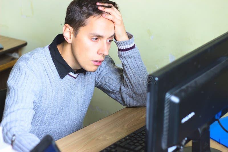 Le type regarde triste l'ordinateur photos stock