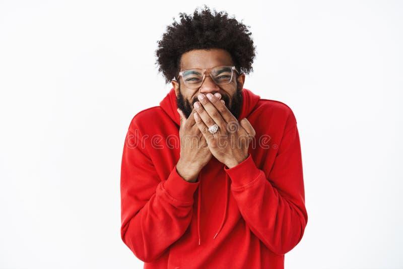 Le type riant sous cape et riant nerveusement comme ami de tour, a fait la position de polisson ravie après projets de la bouche  photographie stock