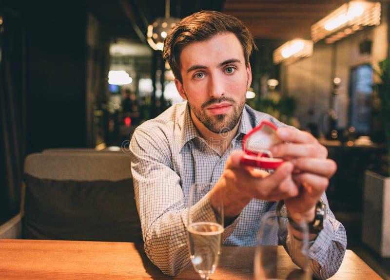 Le type sérieux et barbu s'assied à la table et montre une boîte avec un anneau Il attend une réponse du sien image libre de droits