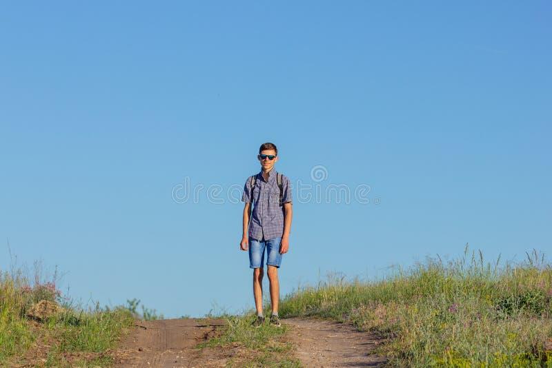 Le type sautant jusqu'au dessus sur la route, concept de voyage photos stock