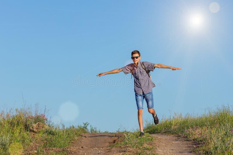 Le type sautant jusqu'au dessus sur la route, concept de voyage images libres de droits