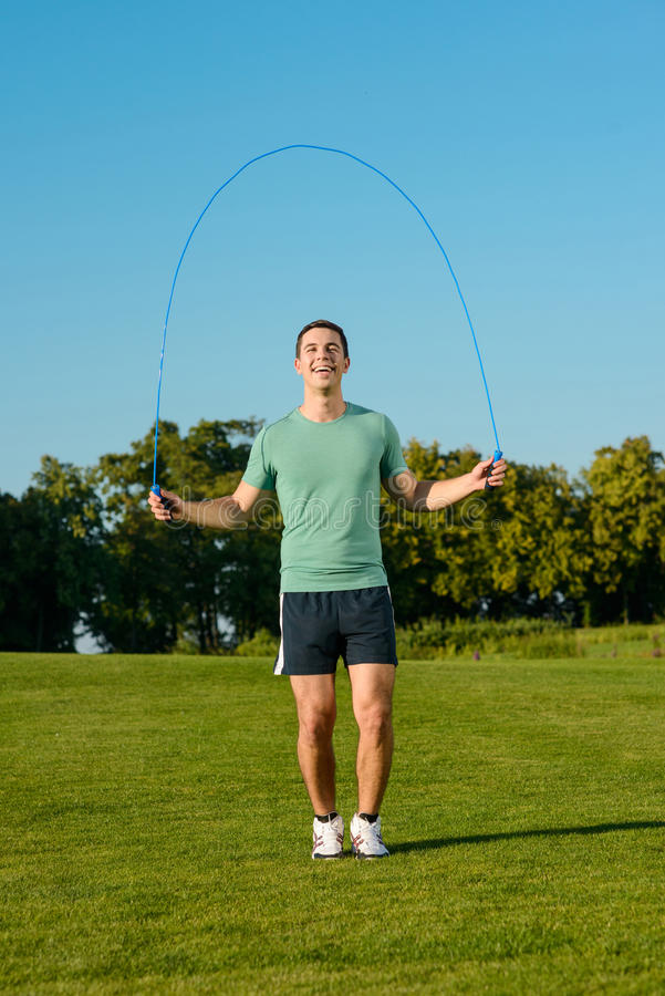 Le type saute sur une corde à sauter sur un pré vert images stock