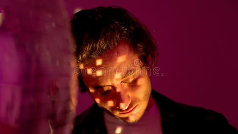 Le type se relaxant près de la discothèque en feu rouge au club, à l'effet alcool et drogues photos stock