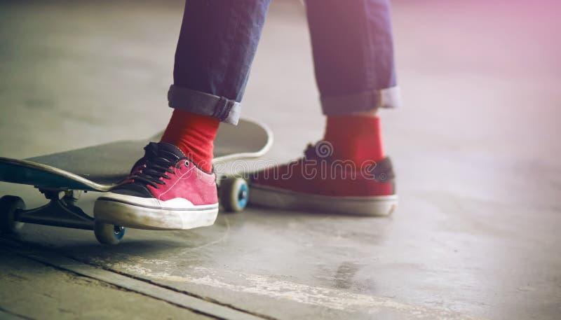 Le type se tient près de son patin et déplace sa jambe photographie stock libre de droits
