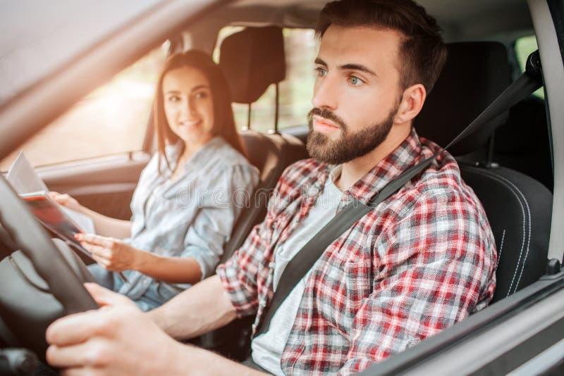 Le type soigneux et gentil conduit la voiture et semble simple Il prête toute son attention à la route La fille est photos stock