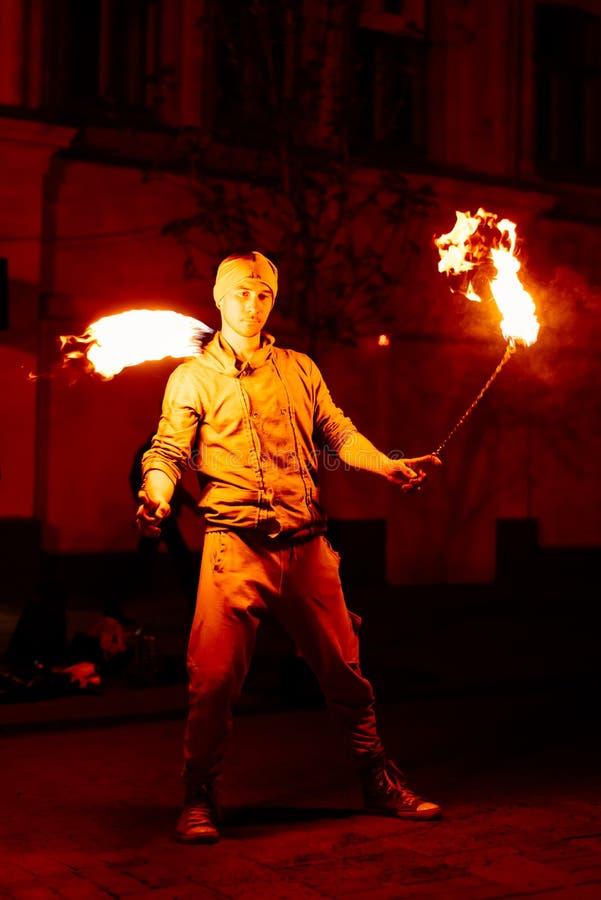 Le type sur la rue exécute avec des torches du feu photo stock