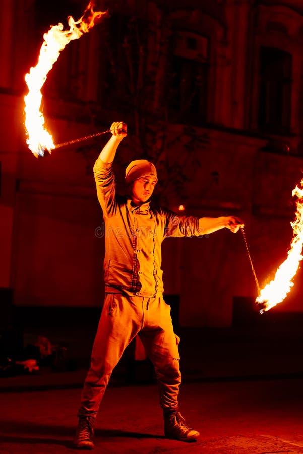 Le type sur la rue exécute avec des torches du feu images stock