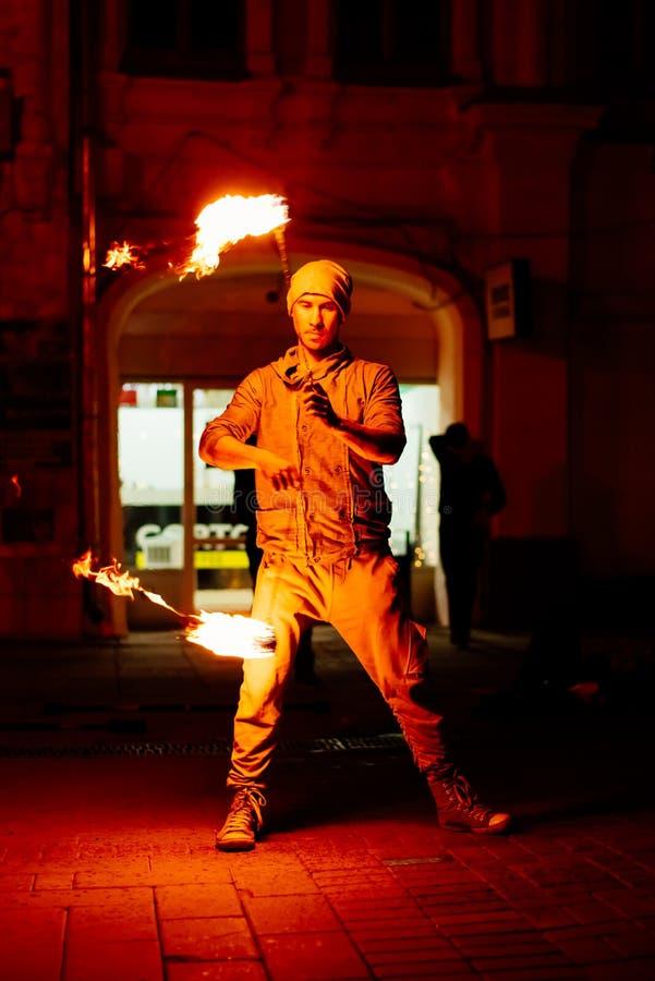 Le type sur la rue exécute avec des torches du feu image stock